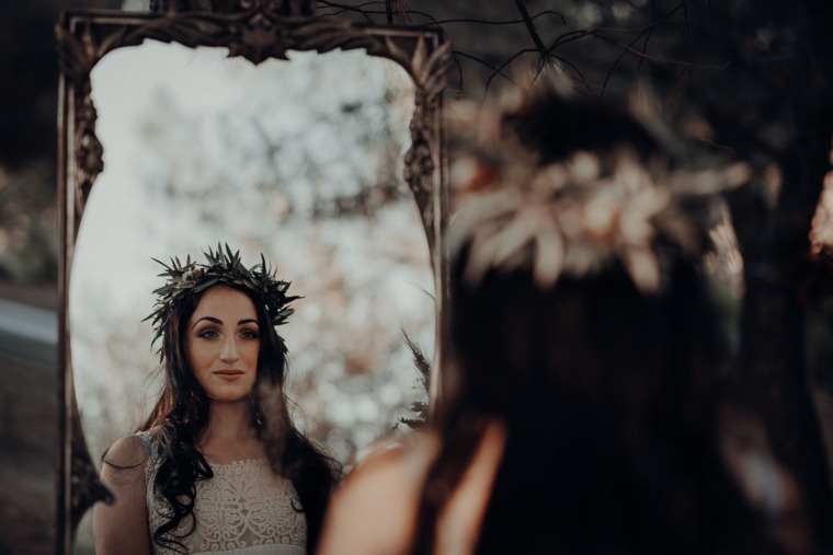 bride with makeup and hairdo looking in the mirror