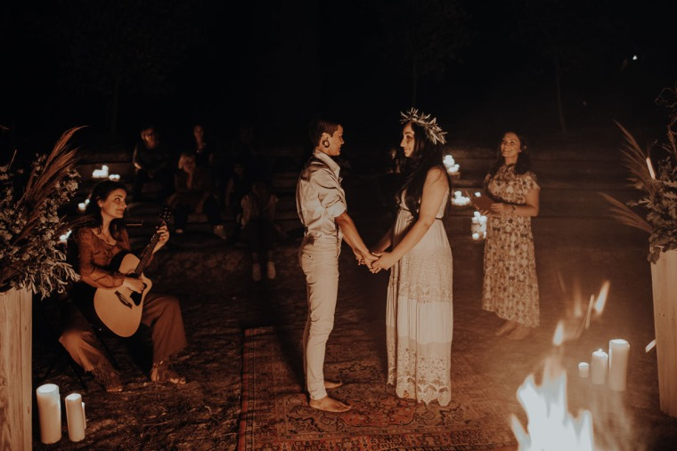 elopement ceremony in tuscany by the fire at night with celebrant and musician