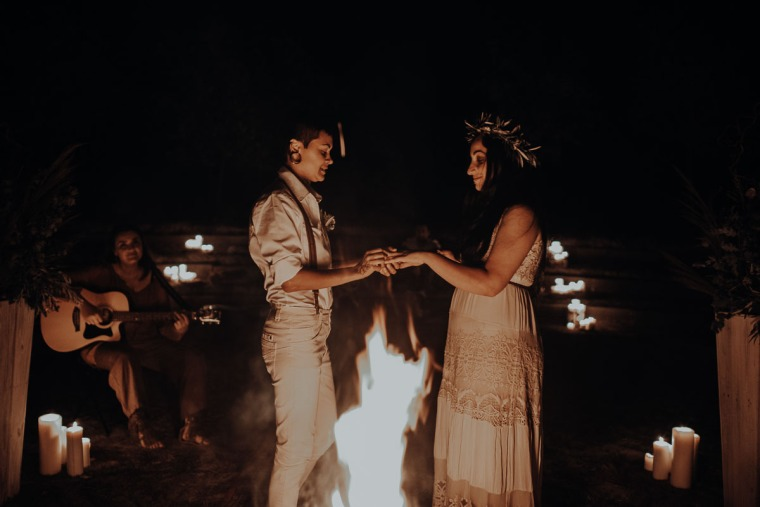 same-sex couple exchanging wedding rings by the campfire