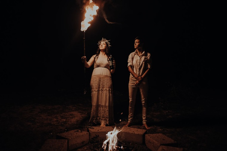 same-sex couple playing with fire in tuscany