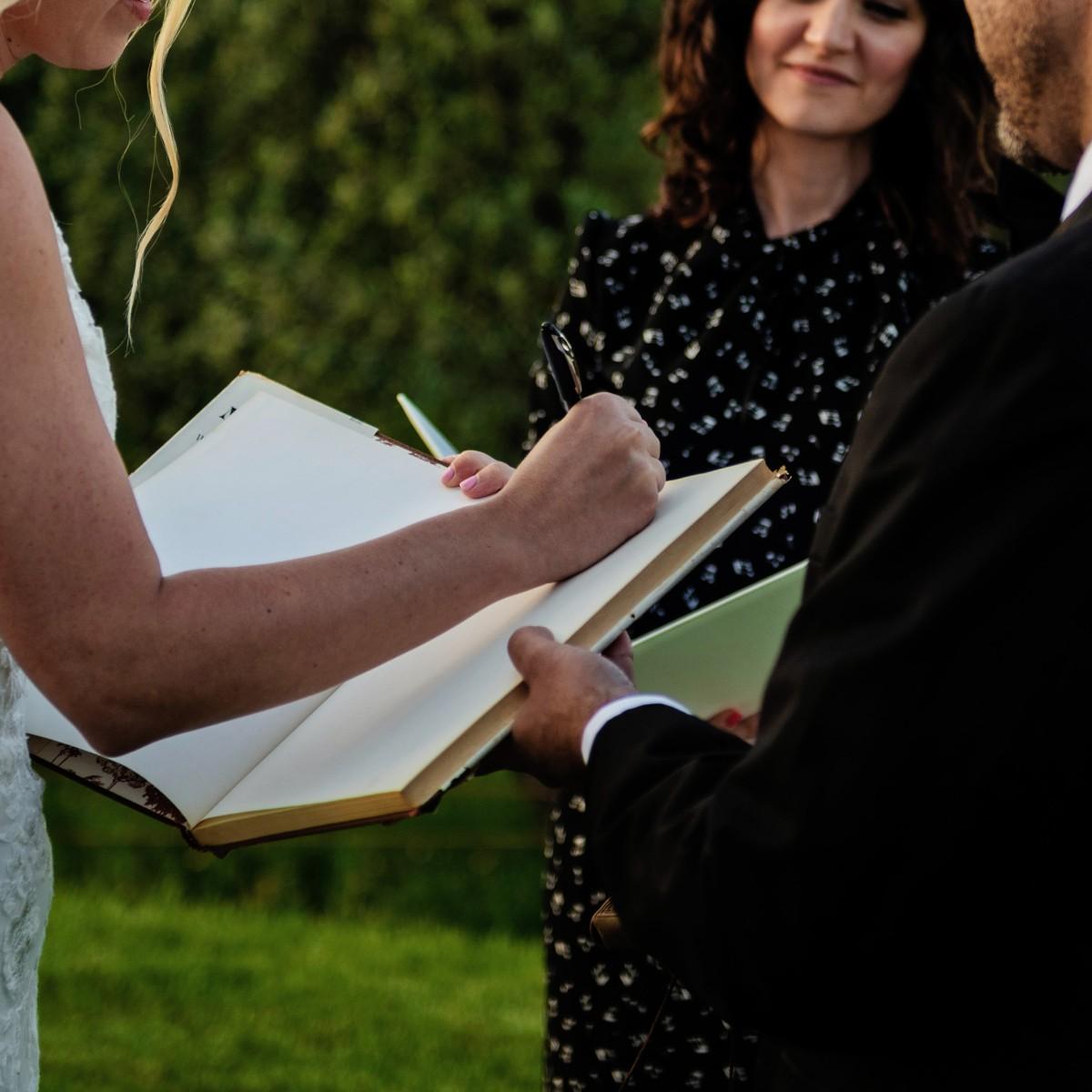 bride-groom-signing-blank-book-ceremony